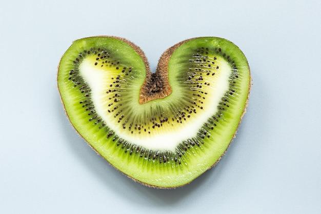 Herzförmige hässliche kiwi in einem schnitt auf grauem hintergrund.