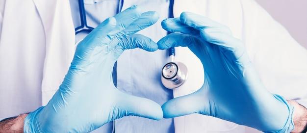 Herzförmige hand in medizinischen handschuhen