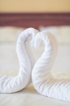 Herzförmige handtücher liegen auf dem bett im hotelzimmer für sie bereit. vertikale fotografie