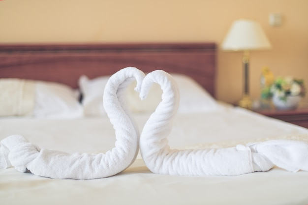 Herzförmige handtücher liegen auf dem bett im hotelzimmer