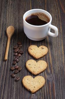 Herzförmige hausgemachte kekse und eine tasse kaffee auf dunklem holztisch