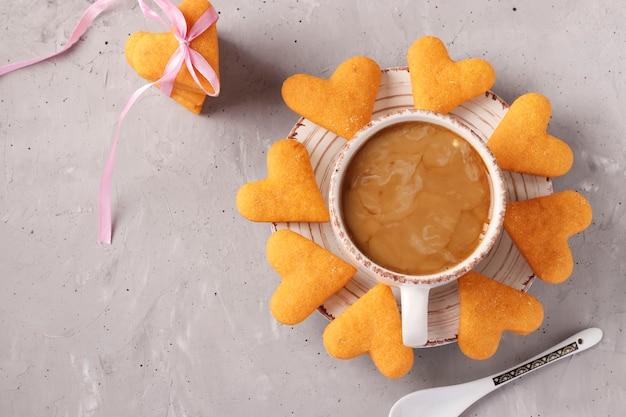 Herzförmige hausgemachte kekse und eine tasse kaffee auf einem grauen betonhintergrund
