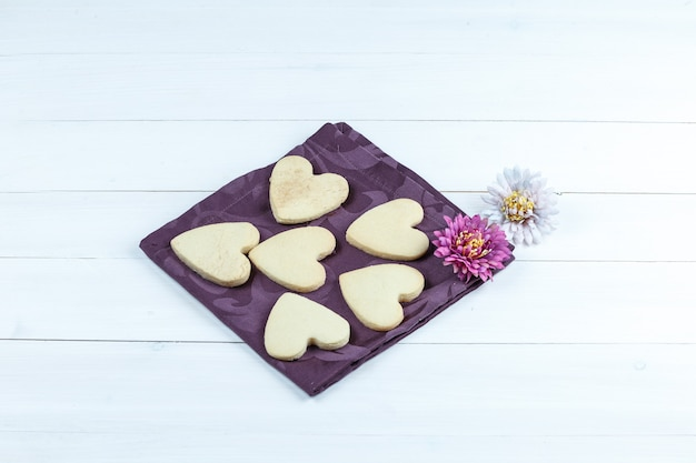 Herzförmige kekse der hohen winkelansicht im tischset mit blumen auf weißem holzbretthintergrund. horizontal