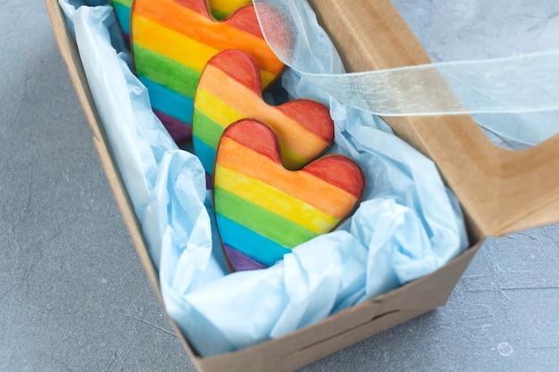 Herzförmige kekse gemalt mit lgbt-regenbogenfahne in geschenkbox.