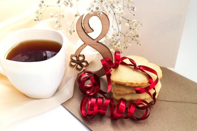 Herzförmige kekse mit einem roten band und einem weißen blumenstrauß. platz für text.