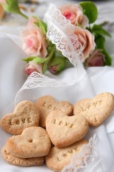 Herzförmige kekse mit liebe. valentinstagbäckerei-herzform-gebäckteig auf einer weißen chiffon- oberfläche mit rosa rosen