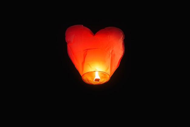 Herzförmige lampe fliegt mit kerzenlicht