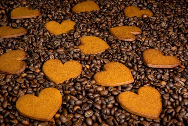 Herzförmige lebkuchenplätzchen auf dem kaffeebohnenhintergrund