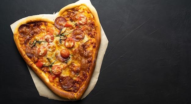 Herzförmige mozzarella-pizza zum valentinstag auf schwarzem isoliertem hintergrund. platz für ihren text.