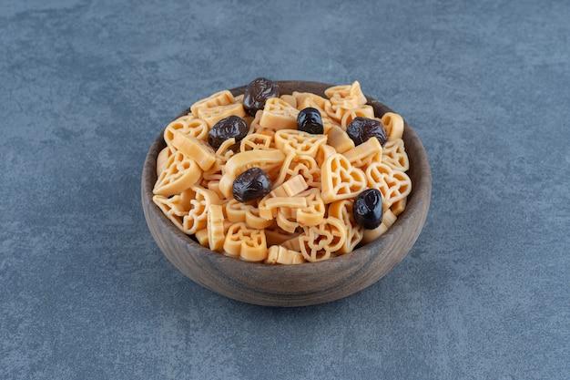 Herzförmige nudeln mit oliven in holzschale.