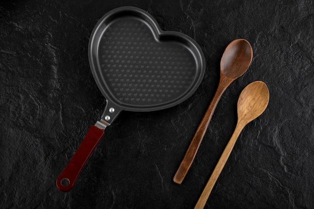 Herzförmige pfanne und holzlöffel auf schwarzer oberfläche