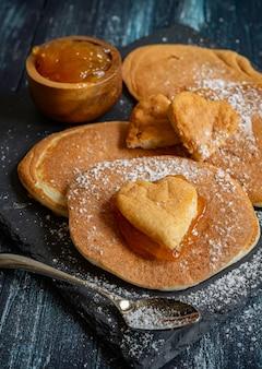 Herzförmige pfannkuchen mit aprikosenmarmelade zum frühstück