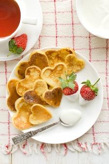 Herzförmige pfannkuchen mit frischen erdbeeren