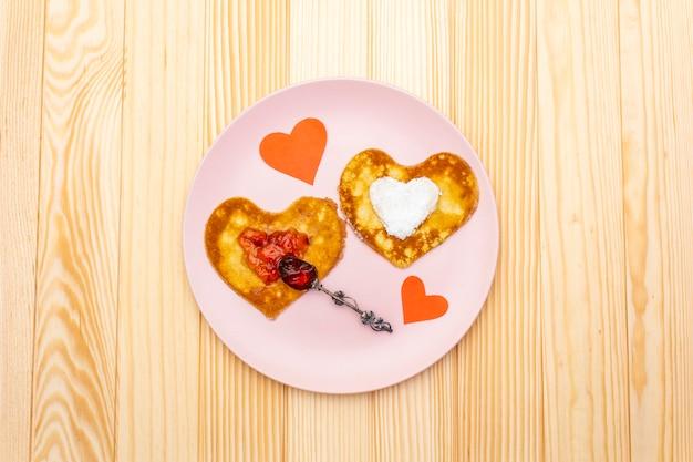 Herzförmige pfannkuchen zum romantischen frühstück mit erdbeermarmelade, silbernem löffel und papierherzen
