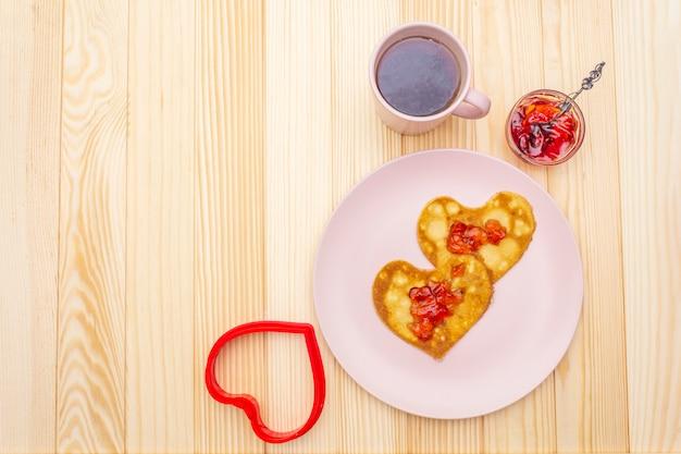 Herzförmige pfannkuchen zum romantischen frühstück mit erdbeermarmelade und schwarzem tee