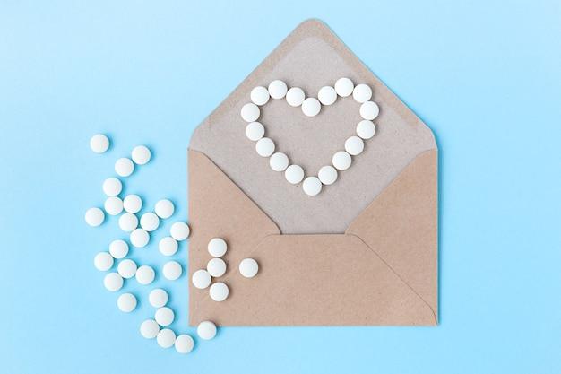 Herzförmige pillen in einem umschlag auf einem blauen hintergrund