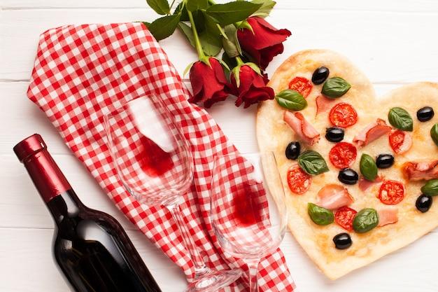Herzförmige pizza-abendessenanordnung der draufsicht