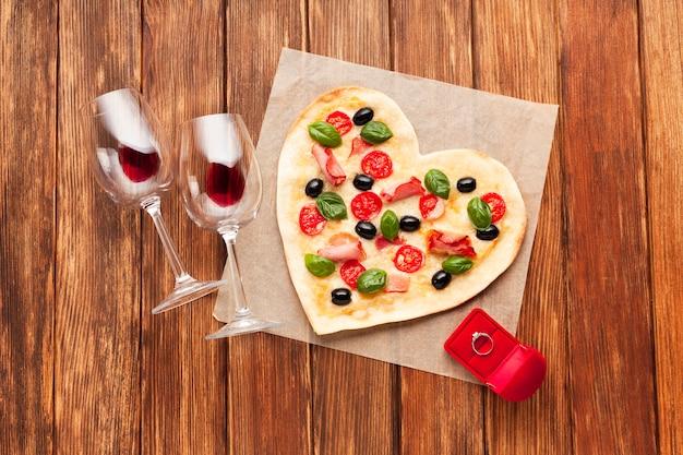 Herzförmige pizza der draufsicht mit ring