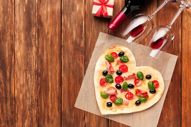 Herzförmige pizza der draufsicht mit wein