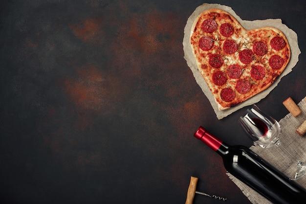 Herzförmige pizza mit mozzarella, gebraten mit einer flasche wein und weinglas. valentinstaggrußkarte auf rostigem hintergrund