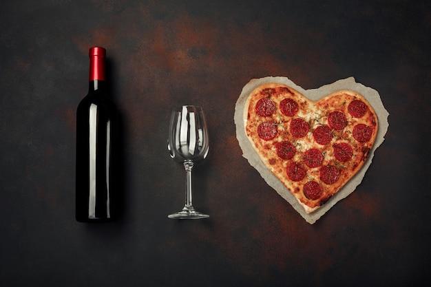 Herzförmige pizza mit mozzarella, wurst und weinflasche.