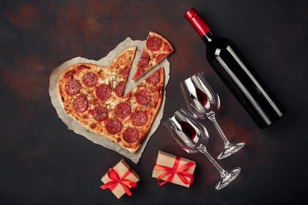Herzförmige pizza mit mozzarella, wurst, weinflasche und zwei weinglas. valentinstaggrußkarte auf rostigem hintergrund.