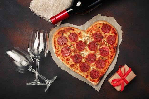 Herzförmige pizza mit mozzarella, wurst, weinflasche, weinglas zwei, geschenkbox auf rostigem hintergrund
