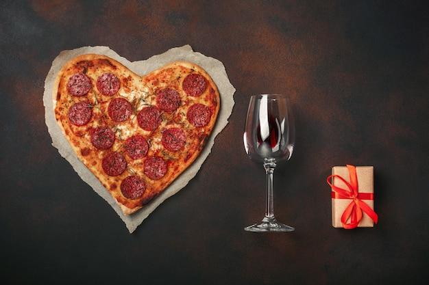 Herzförmige pizza mit mozzarella, wurst, weinglas, geschenkbox auf rostigem hintergrund