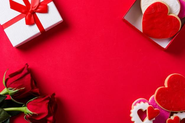 Herzförmige plätzchen für valentinstag und rosen in der geschenkbox auf roter, draufsicht