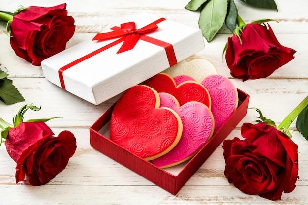 Herzförmige plätzchen und rosen für valentinstag auf weißem holztisch