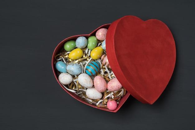 Herzförmige rote geschenkbox mit bunten ostereiern, schwarzer hintergrund. draufsicht.