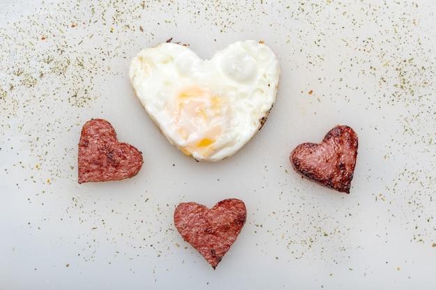 Herzförmige rühreier mit herzförmigen würstchen, kräutern und gewürzen auf einem weißen teller, draufsicht