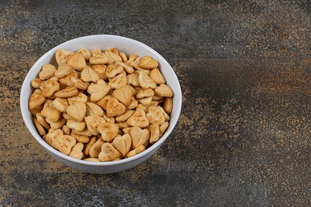 Herzförmige salzige cracker in weißer schüssel.
