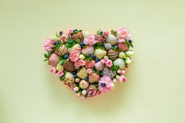 Herzförmige schachtel mit handgemachter erdbeere in schokolade und blumen als geschenk am valentinstag auf gelbem hintergrund
