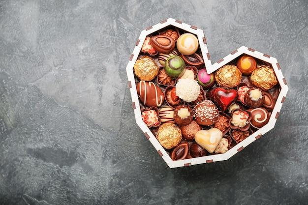 Herzförmige schachtel mit köstlichen bonbons auf grauem hintergrund