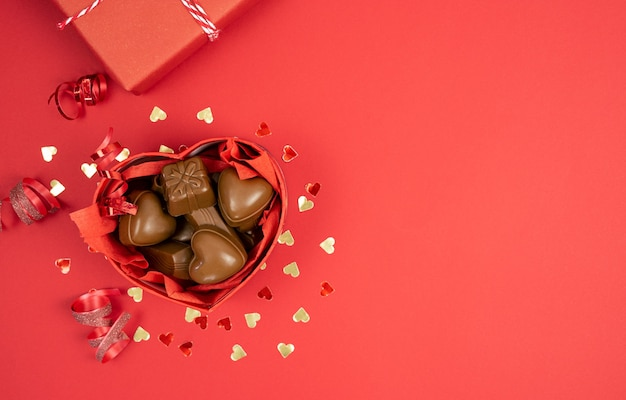 Herzförmige schachtel mit pralinen auf rotem grund. valentinstag