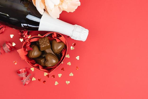 Herzförmige schachtel mit pralinen und champagnerflasche auf rotem grund. valentinstag