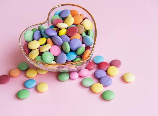 Herzförmige schale mit bunten dragee-süßigkeiten auf einer rosa oberfläche