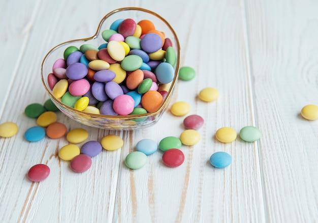 Herzförmige schale mit bunten dragee-süßigkeiten auf einer weißen holzoberfläche