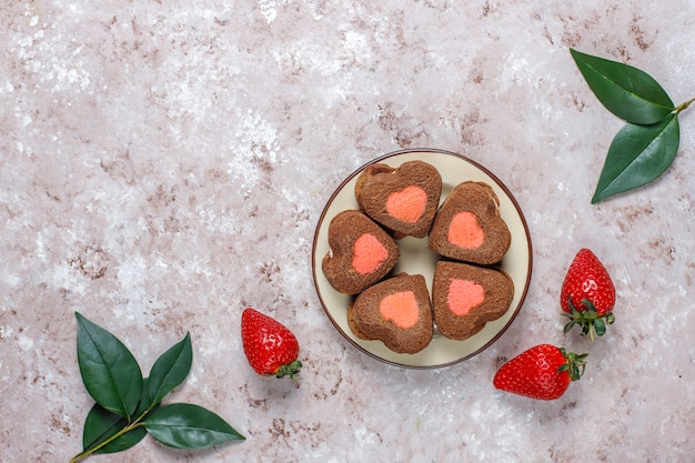 Herzförmige schokoladen- und erdbeerplätzchen mit frischen erdbeeren, draufsicht