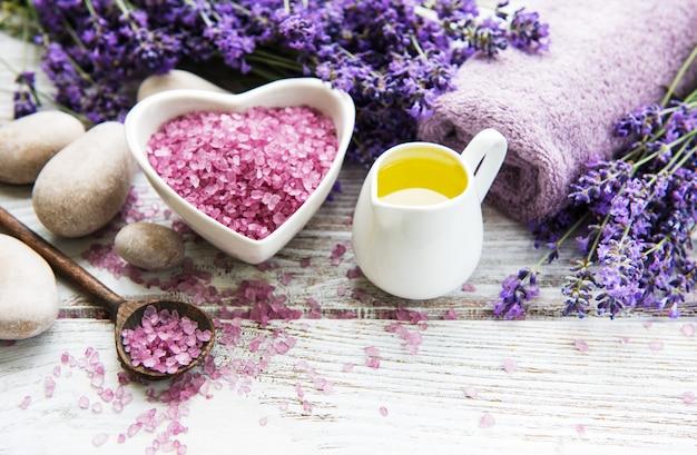Herzförmige schüssel mit meersalz, ölen, seife und frischem lavendel blüht auf einem hölzernen hintergrund