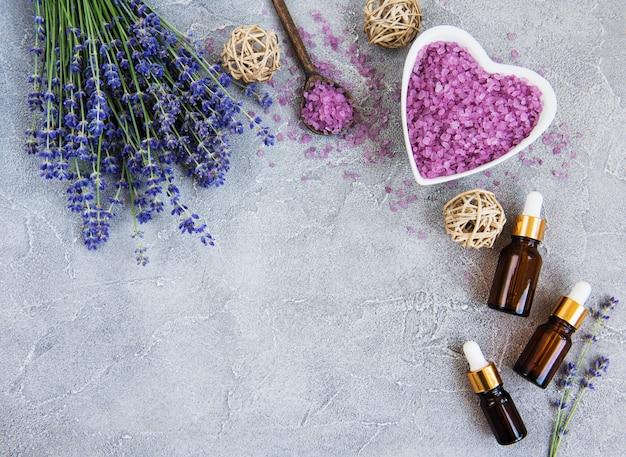Herzförmige schüssel mit seesalz und frischem lavendel blüht auf einem konkreten hintergrund