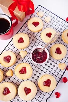 Herzförmige traditionelle linzer-kekse mit erdbeermarmelade auf dem backblech