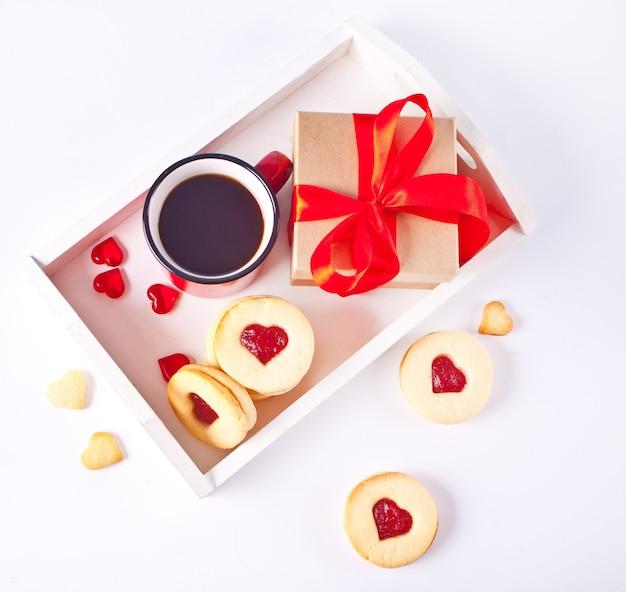 Herzförmige traditionelle linzer-kekse mit erdbeermarmelade, tasse kaffee und geschenkbox. valentinstag konzept. draufsicht.