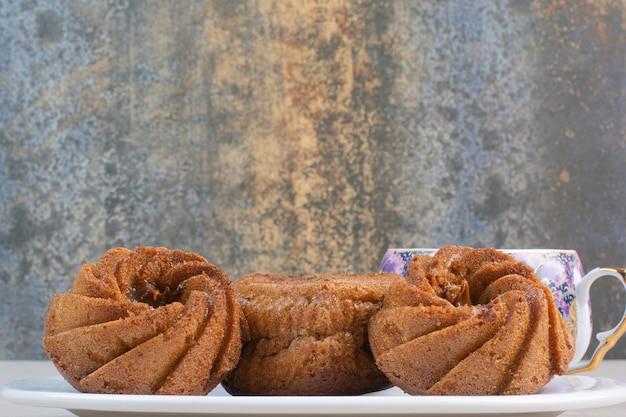 Herzförmige und runde kuchen auf weißem teller.