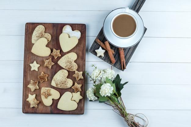 Herzförmige und sternplätzchen auf einem hölzernen schneidebrett mit tasse kaffee, blumen, zimt flach lagen auf einem weißen hölzernen bretthintergrund