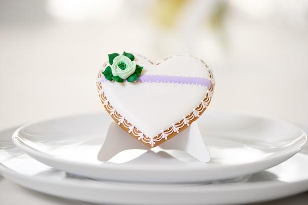 Herzförmiger glasierter keks - verziert mit grüner glasurblume und winzigem muster steht auf einem weißen teller als dekoration für festlichen hochzeitstisch. auf dem weißen restaurant steht ein keks
