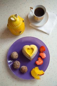 Herzförmiger kalter kuchen ohne backen gefrorene sommersüße veilchenteller gelb hausgemachte zuckerfrei roh
