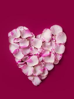 Herzförmiger kranz des feiertags, hergestellt von hellen rosenblättern auf rotem hintergrund, valentinstag oder hochzeitstag
