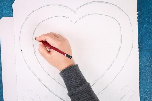 Herzförmiger kranz verzierte künstliche blume, die rosa seidenpapierservietten gemacht wurde